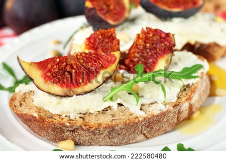Tasty sandwiches with sweet figs and cottage cheese on plate - stock photo