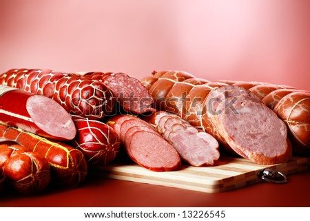 Tasty sausages on the red background. - stock photo