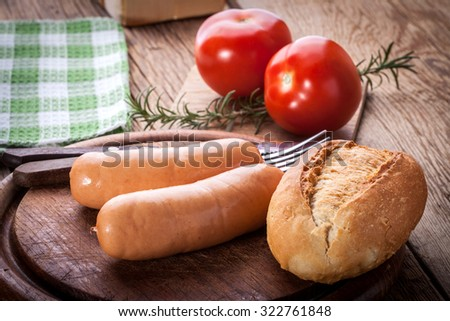 Tasty sausages with bread on a wooden chopping board. - stock photo