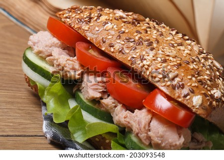Tasty school lunch: a sandwich with tuna and vegetables macro on background of books on the table. horizontal  - stock photo