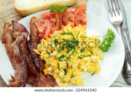 Tasty scrambled eggs with bacon and tomatoes - stock photo