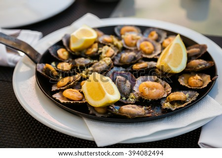 tasty seafood - grilled limpets served with lemon - stock photo