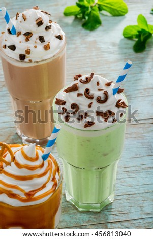 Tasty set of different milkshakes with interesting variations of ingredients: mint and kiwi, vanilla and caramel, chocolate with cocoa. Served drinks on the vintage table. - stock photo