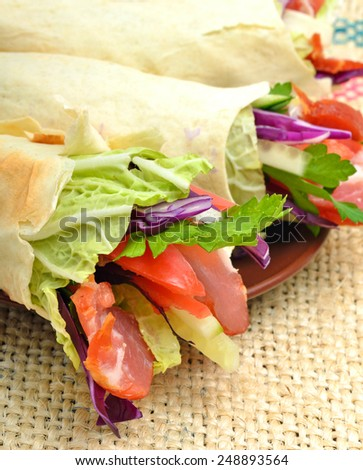 Tasty  shawarma with fresh vegetables and meat, lavash, pita, appetizer on sacking background - stock photo