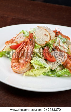 Tasty shrimp salad with vegetables on christmas table - stock photo