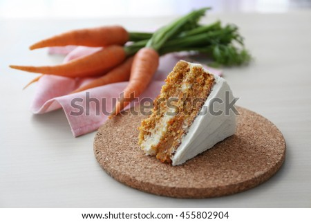 Tasty slice of carrot cake on cork plate