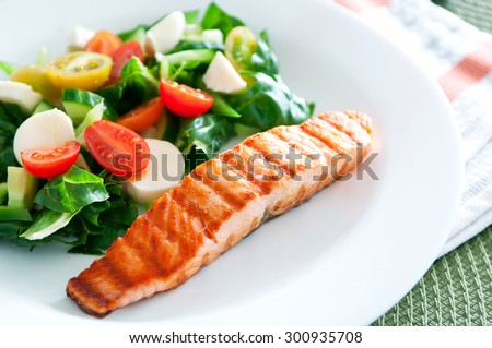 Tasty slice of fried salmon served with mix salad of kale leaves, cherry tomatoes and bocconcini cut in halves, cucumber, served on a white plate. Healthy food. Selective focus, copy space  - stock photo
