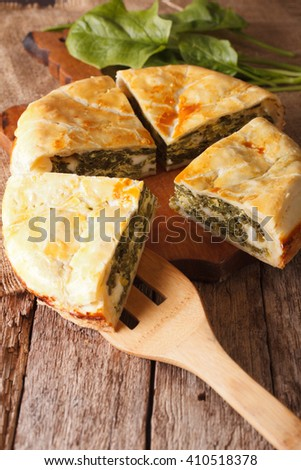 Tasty sliced Greek spanakopita pie close-up on the table. Vertical - stock photo