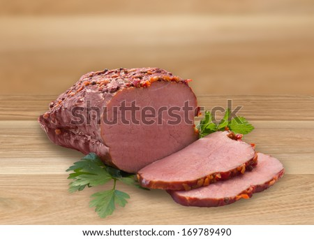 Tasty smoked meat on wooden table surface - stock photo