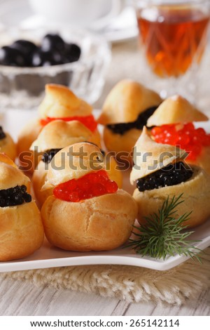 Tasty snack: profiteroles stuffed with red and black caviar on a plate close-up. vertical  - stock photo