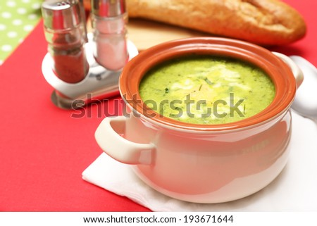 Tasty soup in saucepan on tablecloth, close up