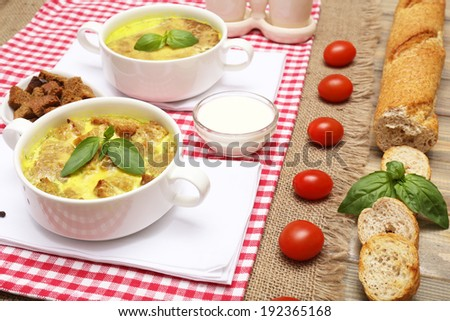 Tasty soup in saucepans on wooden table, close up