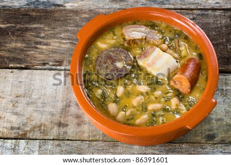 tasty spanish stew made with beans, cabbage and pork meat - stock photo
