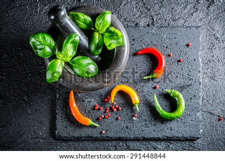 Tasty spices and herbs in mortar - stock photo