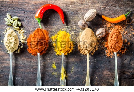Tasty spices and herbs on old spoons - stock photo