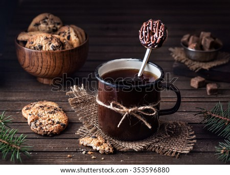 Tasty spoon with doughnut from polymer clay in the mug with tea near chocolate cookies on wooden background  - stock photo