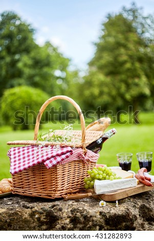 Tasty spring picnic lunch with red wine, baguette, assorted cheese, grapes and spicy sausages with a wicker hamper and checked cloth on a rock in a park