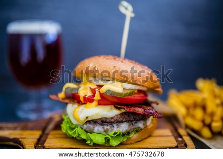 Tasty street food grilled beef burger in crispy shortbread with lettuce and mayonnaise served with beer on small cutting board a rustic wooden table with copyspace
