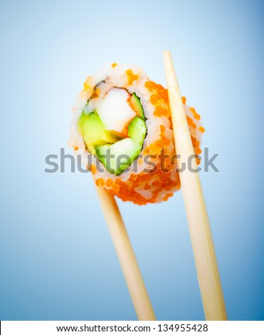 Tasty sushi roll with crab, cucumber, avocado and red caviar in chopsticks isolated on blue background, traditional japanese food - stock photo