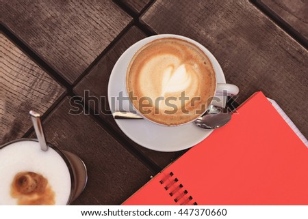 Tasty sweet cappuccino cup with foam and latte glass on brown wooden table on the summer cafe terrace. Coffee cup on table in the restaurant and notebook with red paper, top view - stock photo