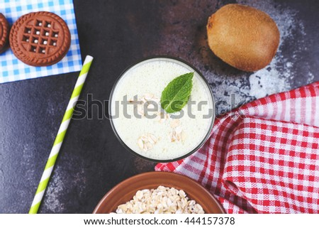 Tasty sweet diet milkshake with kiwi and mint leaf, rasberries and oatflakes on the black table in the cafeteria or restaurant. Glass with tasty smoothie breakfast and green paper straw. - stock photo
