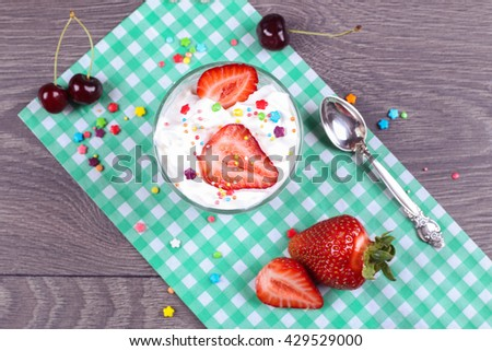 Tasty sweet ice cream dessert in the glass and Ice cream spoon with ripe strawberries and cherries on the paper green napkin on the gray wooden table. Candies with ice cream in sundae - stock photo
