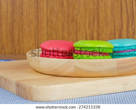 Tasty Sweet Macaroons on wooden background.