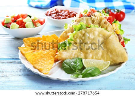 Tasty taco with nachos chips and vegetables on plate on table close up - stock photo
