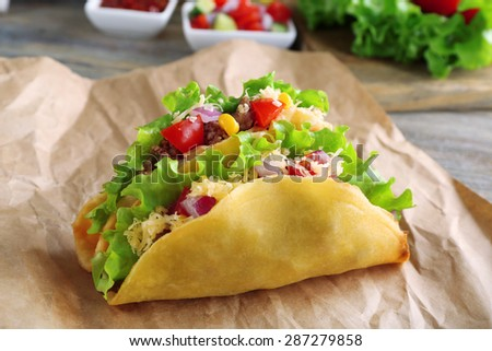 Tasty taco with vegetables on paper on table close up - stock photo