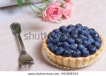 Tasty tart with blueberries and pink roses - stock photo