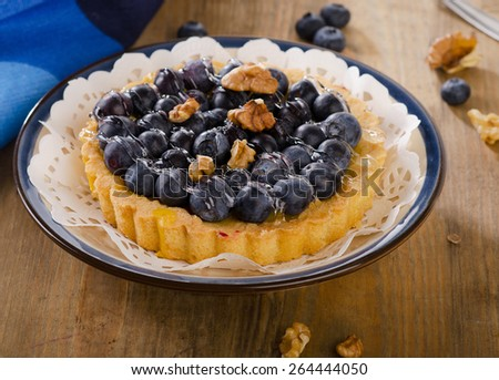 Tasty tart with blueberries  on a wooden table. - stock photo