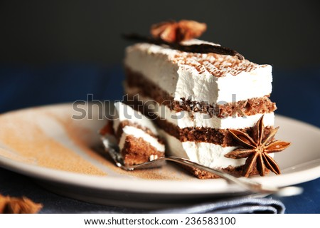 Tasty tiramisu cake on plate, on black background - stock photo