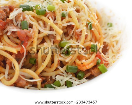 Tasty tomato pasta with grounded meat and vegetables, isolated on white, close up, restaurant dish