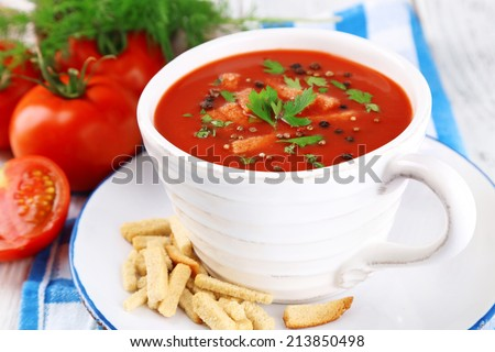 Tasty tomato soup with croutons on table close-up