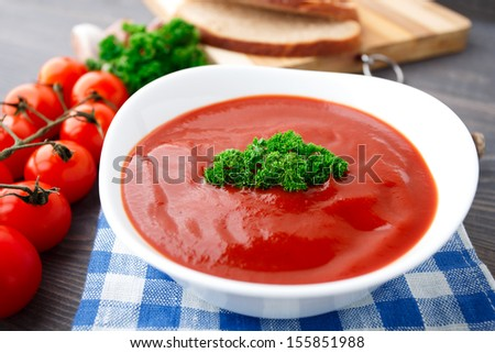 Tasty tomato soup with herbs - stock photo