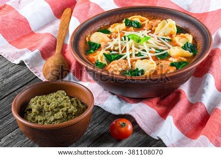 tasty tortellini soup with italian sausages, spinach, tomato, shredded parmesan cheese and spices in a clay rustic bowl and pesto sauce in a small bowl, close-up - stock photo