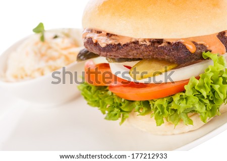 Tasty traditional cheeseburger with a ground beef patty topped with melted cheese and served with onion rings, tomato and curly leaf lettuce on a round white bread roll, close up view