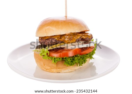 Tasty traditional cheeseburger with a ground beef patty topped with melted cheese and served with onion rings, tomato and curly leaf lettuce on a round white bread roll, close up view - stock photo
