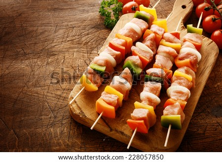 Tasty uncooked meat kebabs in a country kitchen with cubed meat, diced colorful bell peppers, onion and tomato on a wooden chopping board ready to grill on a wooden scored grungy counter top - stock photo