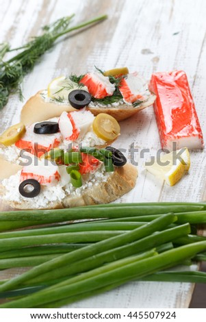 Tasty various italian sandwiches with seafood against rustic wooden background. Crostini with cheese, crab sticks, olives, and herbs, close up with selective focus