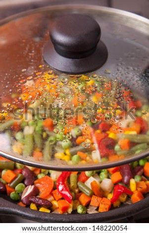 Tasty vegetables in pan, under glass lid  - stock photo