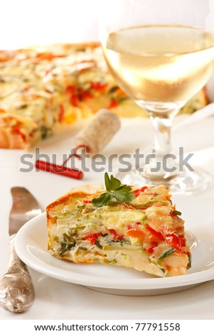 Tasty vegetables pie on a plate and glass of wine. - stock photo