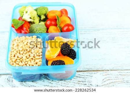 Tasty vegetarian food in plastic box on wooden table - stock photo