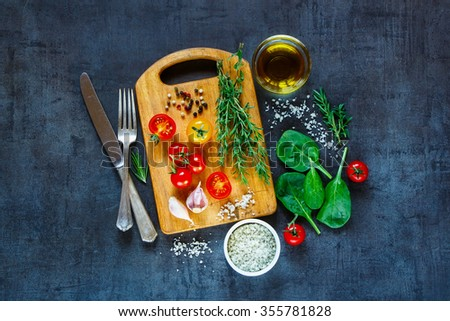 Tasty vegetarian ingredients, olive oil and seasoning on rustic wooden cutting board over dark vintage background, top view. Healthy food, vegan or diet nutrition concept. - stock photo