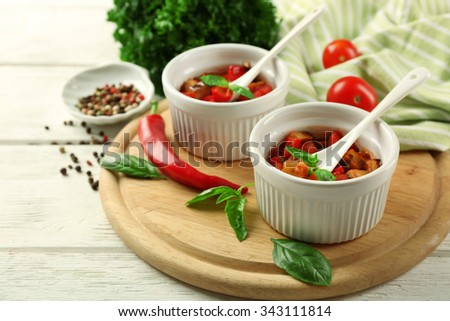 Tasty vegetarian ratatouille made of eggplants, squash, tomatoes in bowls on wooden table background - stock photo