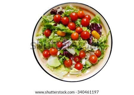 Tasty vegetarian salad with red and yellow cherry tomatoes, arugula, cabbage and lettuce