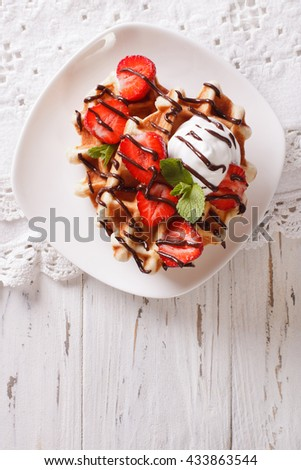 Tasty waffles with strawberries, whipped cream and chocolate frosting close up. Vertical view from above