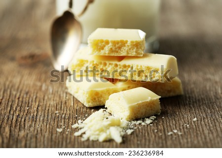Tasty white porous chocolate and glass of milk, on wooden table. Close up - stock photo