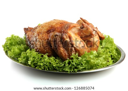 Tasty whole roasted chicken on plate with lettuce leaves, isolated on white
