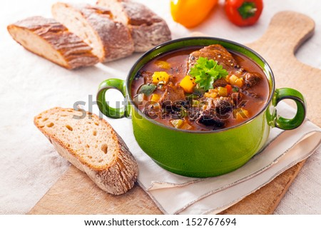 Tasty winter stew in a green metal pot with meat and assorted vegetables in a rich gravy served with fresh crusty bread on a wooden chopping board - stock photo